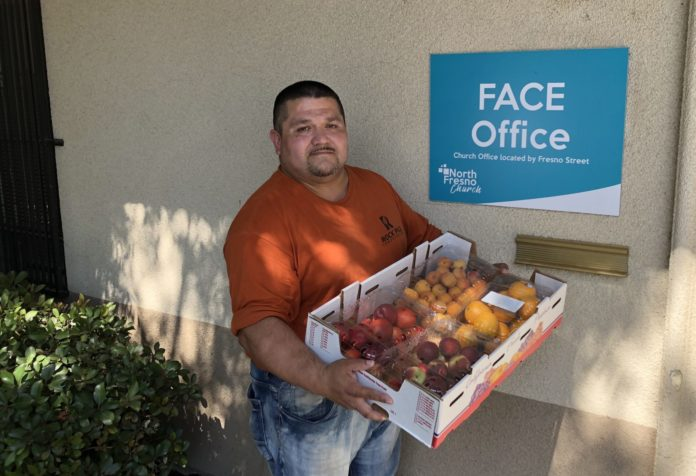 leonard holding fruit outside FACE office